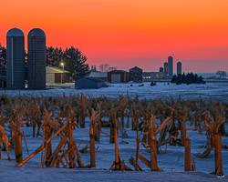 snow filled corn fields in rural Wisconsin as the sun sets orange over the farm silos
