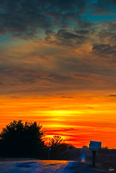 An amazing colorful sunset over rural road. Like a rainbow in the sky, the colors ranged orange to cyan.