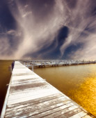 long pier at sunset on lake with golden water and whispy clouds