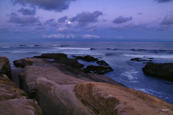 Rocky shoreline of Pacific Beach in San Diego, California at sunrise and moonset over the Pacific Ocean